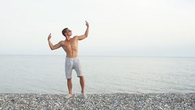 Portrait of a handsome, muscular guy withsunglasses sea in background. Masculine hard body man in sunglasses at beach with mountauns on background stock video