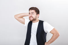 Portrait of handsome pensive brunette man in white shirt on gray background. guy thinks Royalty Free Stock Photo