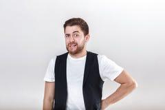 Portrait of handsome pensive brunette man in white shirt on gray background. guy thinks Stock Photo