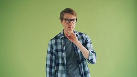 Portrait of handsome person making hush gesture touching mouth with finger. Asking for silence standing against green background. Guy is wearing glasses and stock video footage