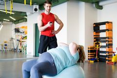 Obese Woman training in Fitness Club. Portrait of handsome personal fitness instructor holding timer while watching obese women doing crunches on fitness ball Stock Image
