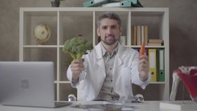 Portrait of handsome positive man in white robe looking in the camera proposing carrot and broccoli. Skillful doctor in. Portrait of handsome positive man in stock footage