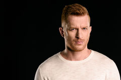 Portrait of handsome redhead man looking at camera. Isolated on black Royalty Free Stock Image