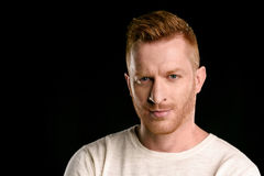 Portrait of handsome redhead man looking at camera. Isolated on black Stock Images