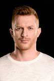 Portrait of handsome redhead man posing and looking at camera. Isolated on black Royalty Free Stock Photos