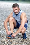 Handsome runner in his 40s tying his shoes. Portrait of handsome runner in his 40s tying his shoes Royalty Free Stock Images