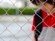 Portrait of handsome sad boy behind fence mesh netting. Emotions concept - sadness, sorrow, melancholy. Fashion & beauty concept stock photography