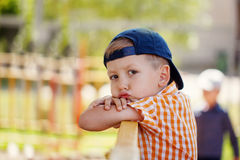 Portrait of a handsome sad little boy in cap looking at camera in park in sunny and summer day. Stock Photo
