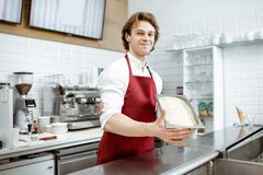 Salesman with ice cream in the shop. Portrait of a handsome salesman or confectioner in red apron holding tray with ice cream in the shop royalty free stock photos