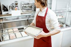 Salesman with ice cream in the shop. Portrait of a handsome salesman or confectioner in red apron holding tray with ice cream in the shop royalty free stock photo