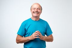 Portrait of a handsome senior man in blue t-shirt laughing Stock Images