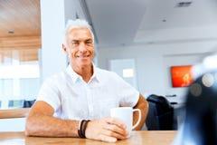Portrait of a handsome senior man indoor. Portrait of a handsome senior man having tea and smiling indoor royalty free stock photos