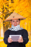 Portrait of a handsome serious hispanic young business guy wearing an asian conical hat pointing in front of him his Stock Image