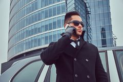 Portrait of a bodyguard in a stylish suit. Portrait of a handsome serious male bodyguard in sunglasses talking on the phone near car outdoors royalty free stock photos