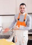 Portrait of handsome skilled workman. Portrait of young handsome skilled workman at residential kitchen Stock Photo