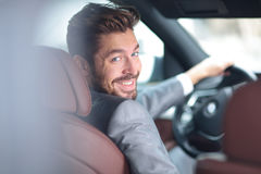 Portrait of an handsome smiling business man driving his car Stock Images