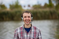 Portrait of a smiling customer service operator wearing a headset. Portrait of a handsome smiling customer service operator wearing a headset standing on river Royalty Free Stock Images