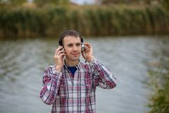 Portrait of a smiling customer service operator wearing a headset. Portrait of a handsome smiling customer service operator wearing a headset standing on river Stock Images