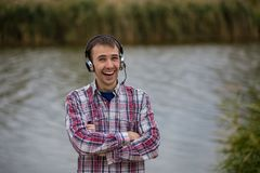 Portrait of a smiling customer service operator wearing a headset. Portrait of a handsome smiling customer service operator wearing a headset standing on river Royalty Free Stock Photos