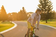 Portrait of handsome smiling man on bicycle. Attractive caucasian student enjoying riding bike on country road. Summer holiday concept Stock Photography