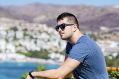 Portrait of handsome smiling man with black sunglasses on a sea background. Portrait of handsome  young man with black sunglasses Royalty Free Stock Photos