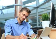 Portrait of handsome smiling man in casual shirt taking notes at workplace. Portrait of handsome smiling man in casual shirt taking notes at workplace Stock Images