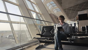 Portrait of handsome smiling man in casual wear, with his tablet while sitting in the hall of the airport terminal. Portrait of handsome smiling man in casual stock video