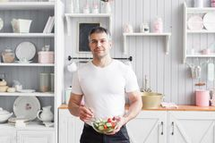 Portrait of handsome smiling man chopping vegetables in the kitchen. The concept of eco-friendly products for cooking. royalty free stock photos