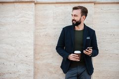Portrait of a handsome smiling man holding coffee cup. While standing and leaning on a wall outdoors Stock Photography