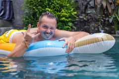 Portrait of handsome smiling man on the inflatable mattress in swimming pool at sunny day. Bali. Royalty Free Stock Photos