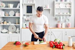 Portrait of handsome smiling man at kitchen. cooking and home concept - close up of male hand chopping cucumber on. Portrait of handsome smiling man at kitchen royalty free stock photography