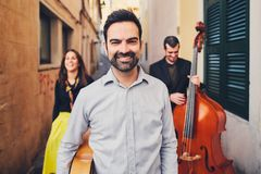 Portrait of handsome smiling man in an old street. In the background of two musicians with a double bass and a singer. A man with. Portrait of handsome smiling royalty free stock photography
