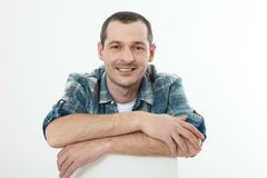 Portrait handsome smiling man in shirt sitting at home Stock Photo