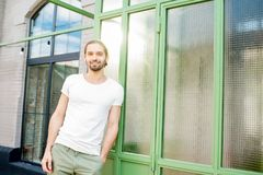 Man portrait outdoors. Portrait of a handsome smiling man in white t-shirt standing near the green wall outdoors royalty free stock photo