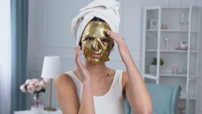 Portrait of handsome smiling woman fixing rejuvenating cosmetic golden tissue mask on face. Portrait of handsome smiling woman with towel on head fixing stock video