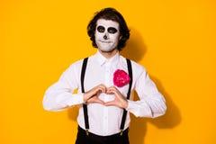 Portrait of handsome spooky creepy cheery amorous affectionate guy gentleman zombie showing heart shape romance feelings