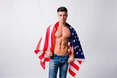 Portrait of handsome sportive confident athletic nude guy wearin. G jeans, he is holding american flag on his shoulders and back, isolated on grey background Stock Photography