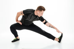 Portrait of a handsome sportsman doing stretching exercises before jogging. Portrait of a young healthy sportsman doing stretching exercises before jogging Stock Photo