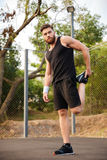 Portrait of a handsome sportsman stretching legs outdoors. Portrait of a handsome bearded sportsman stretching legs outdoors Royalty Free Stock Photo