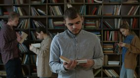 Handsome hipster student reading a book in library stock footage