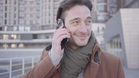 Portrait of handsome successful man in brown coat standing in the city street talking by mobile phone. Urban cityscape. Portrait of handsome confident man in stock video