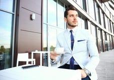 Portrait of handsome successful man drink coffee, business man having breakfast sitting on beautiful terrace Stock Photos