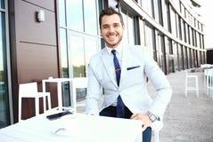 Portrait of handsome successful man drink coffee, business man having breakfast sitting on beautiful terrace Stock Photo