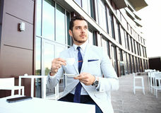 Portrait of handsome successful man drink coffee, business man having breakfast sitting on beautiful terrace Royalty Free Stock Images