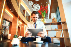 Portrait of handsome successful man drink coffee and look to the digital tablet screen sitting in coffee shop, business. Man having breakfast at hotel lobby royalty free stock images