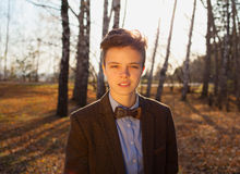 Portrait of a handsome teen boy. Handsome hipster guy man on background of autumn forest Stock Image