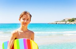 Handsome teenage boy with swim board on the beach. Portrait of handsome teenage boy with rainbow swim board on the beach stock images