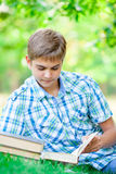 Portrait of handsome teenager reading books on the wonderful par Stock Images