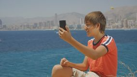 Portrait of handsome teenager in red t-shirt and shorts making smartphone video call on sea coast city skyline. Background stock video footage