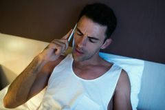 Portrait of handsome upset young man using a mobile phone in the. White bed Royalty Free Stock Photo